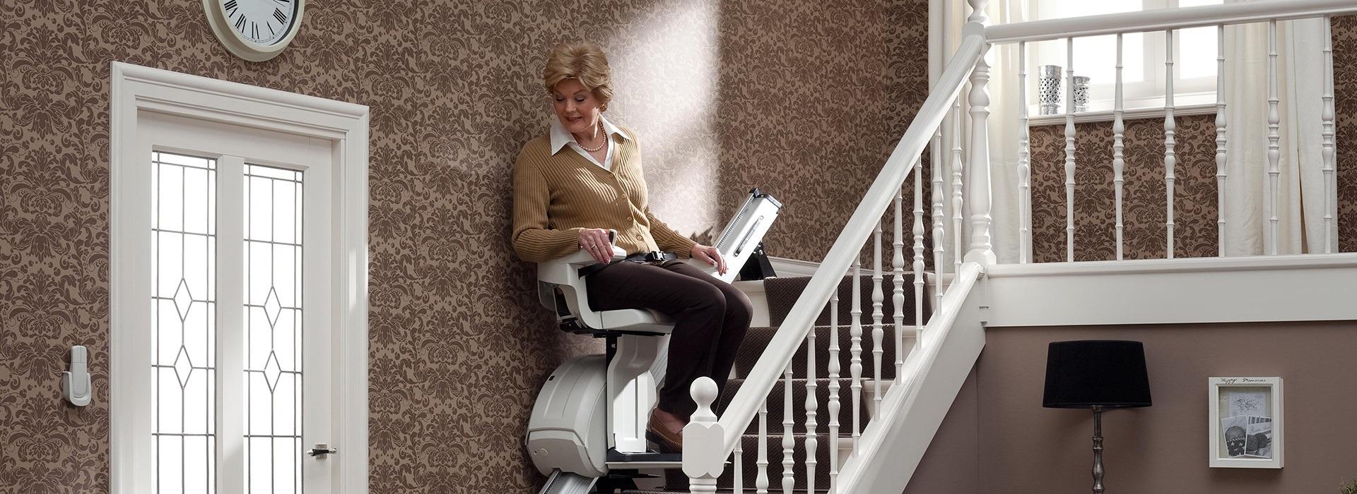 Treppenlift auf dem eine Frau fährt.